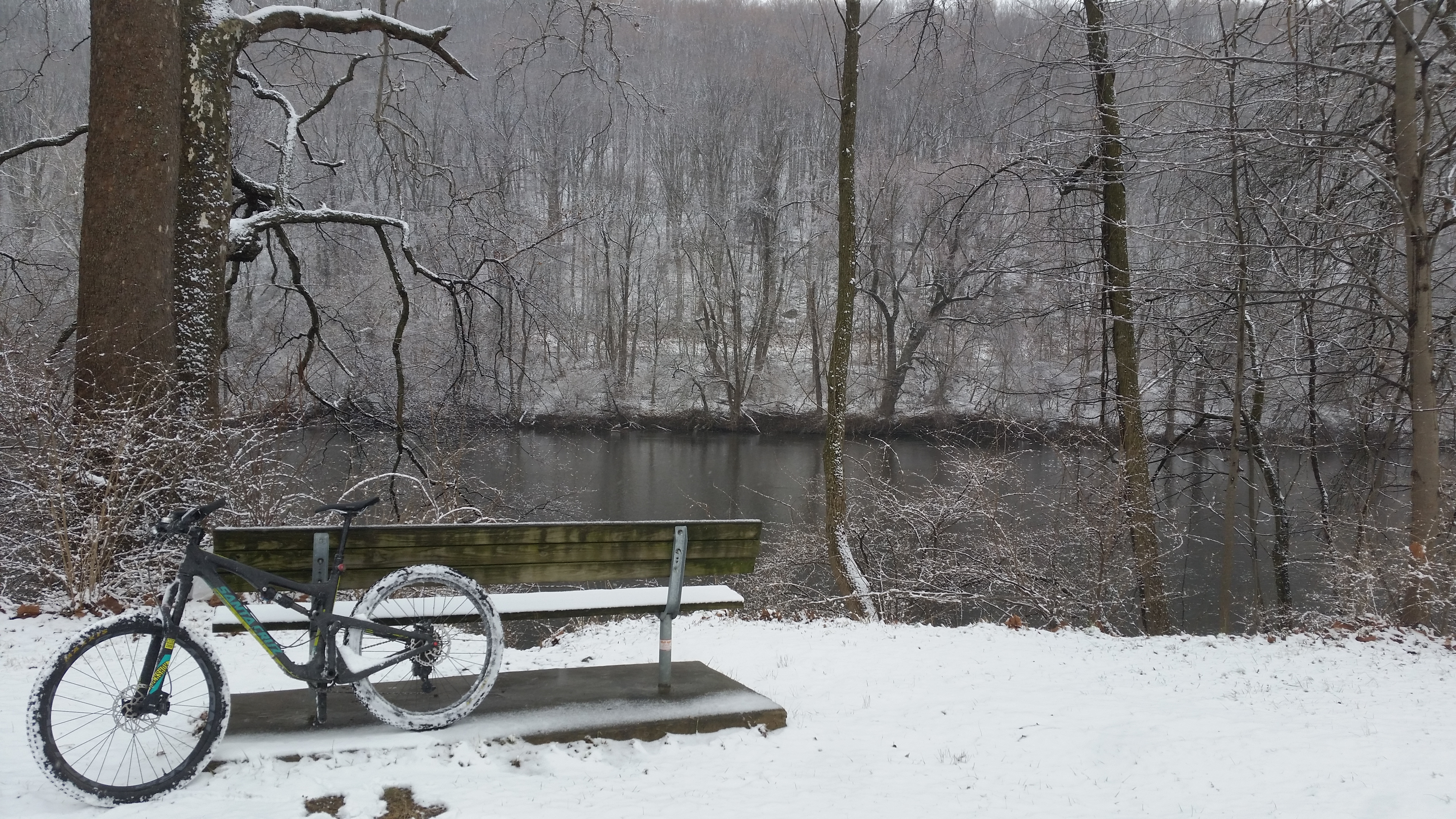 bike leans on a bench. with river and snowy woods in background