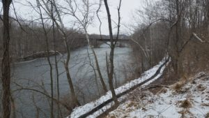 wooded winter river with bridge in distance