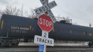 railroad crossing sign with tanker car in background