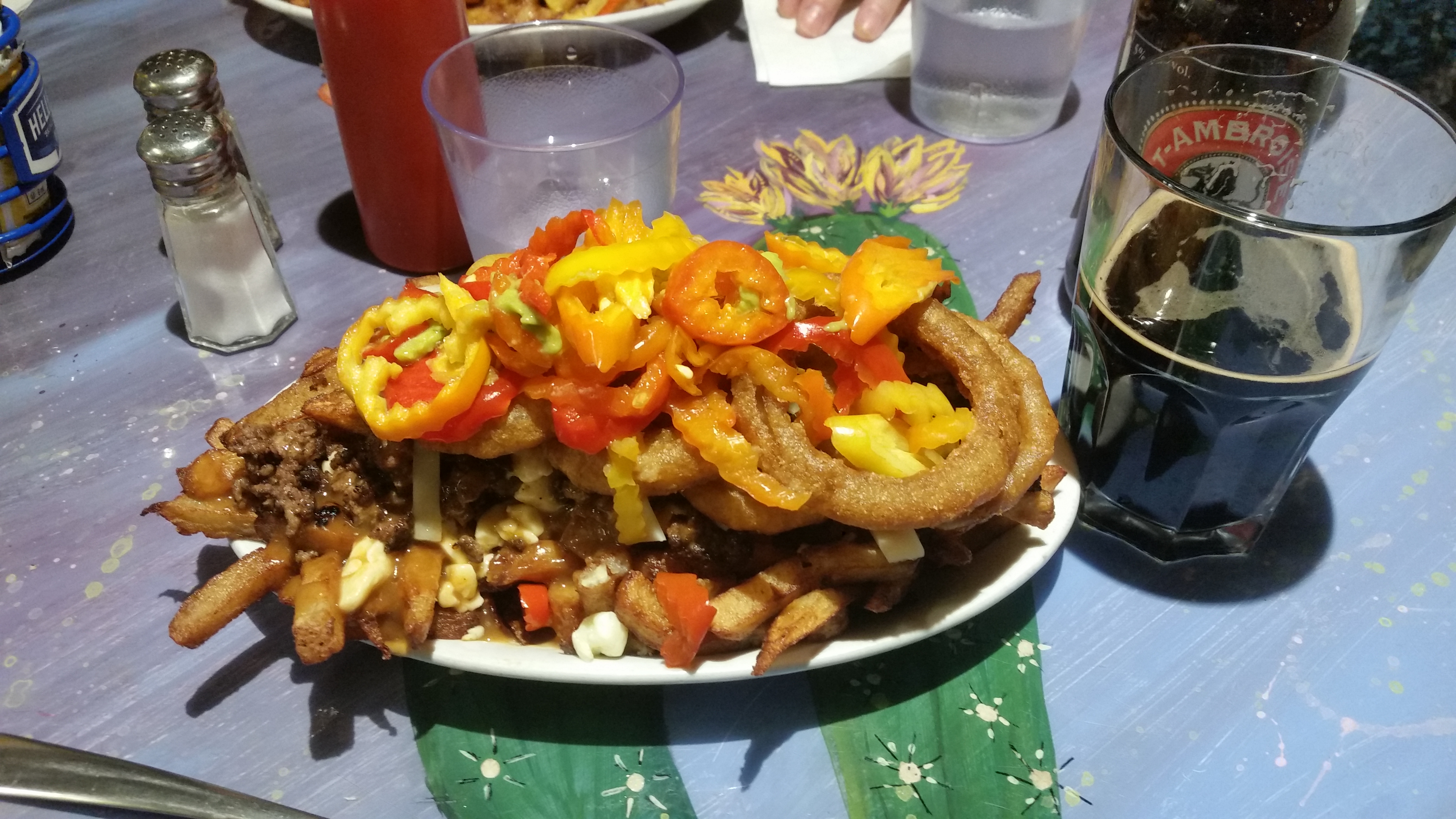 a plate of poutine with hot peppers