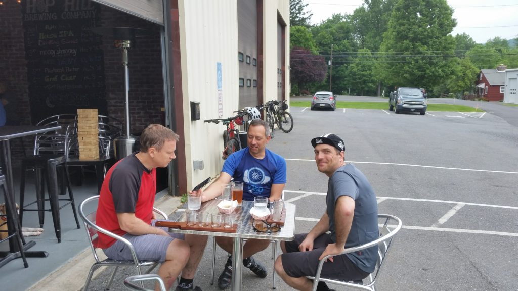 three men drink beer at outdoor table